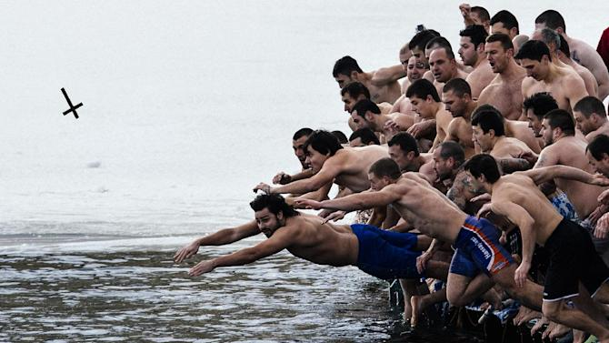 Bulgarians dive into the icy waters of a lake to catch a cross in Sofia as part of Epiphany Day celebrations on January 6, 2015