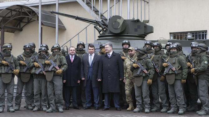 President of Ukraine Petro Poroshenko, centre right, stands next to the head of the National Anti-Corruption Bureau Artem Sytnyk, centre left,  during a ceremony of oath taking by the officers of the National Anti-Corruption Bureau's Special Operations Department, in Kiev, Ukraine, Tuesday, Feb. 9, 2016. (Markiv Mykhailo/Pool Photo via AP)