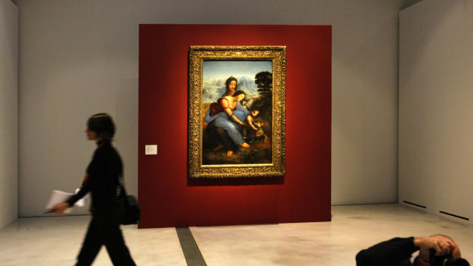 """A woman walk past """"La Vierge, l'Enfant Jesus et Sainte Anne"""" by Leonard de Vinci in the Louvre Museum in Lens, northern France, Monday, Dec. 3, 2012. The museum in Lens, to open the 12 Dec, is part of a strategy to spread art beyond the traditional bastions of culture in Paris. (AP Photo/Michel Spingler)"""