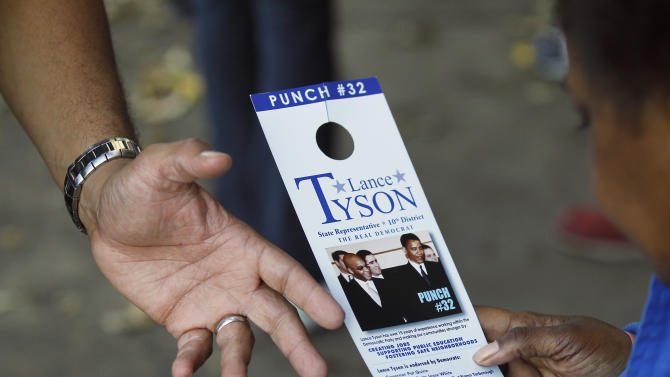 """In this Oct. 24, 2012 photo, Unity Party candidate Lance Tyson, points to his campaign literature showing him and President Barack Obama as he campaigns in the Illinois 10th legislative district in Chicago. Tyson is challenging Derrick Smith, a former state representative indicted on federal bribery charges - and on the ballot as a Democrat - who is fighting to regain Illinois' 10th legislative district seat he was expelled from in August. A victory for Smith could be another embarrassment for a party and a state that already have a reputation for corruption, party leaders say, and they are going to great lengths to defeat Smith. The district's Democratic party committeemen announced a new political party called the """"10th District Unity Party"""" and selected Tyson to take on Smith. (AP Photo/Charles Rex Arbogast)"""