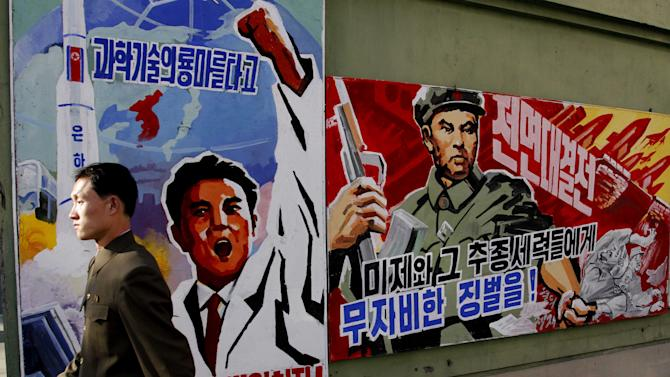 "FILE - In this March 26, 2013 file photo, a North Korean man walks past propaganda posters in Pyongyang, North Korea, that threaten punishment to the ""U.S. imperialists and their allies.""  As tensions rise on the Korean Peninsula, one thing remains certain: All sides have good reason to avoid an all-out war. The last one, six decades ago, killed an estimated 4 million people.   (AP Photo/Kim Kwang Hyon, File)"