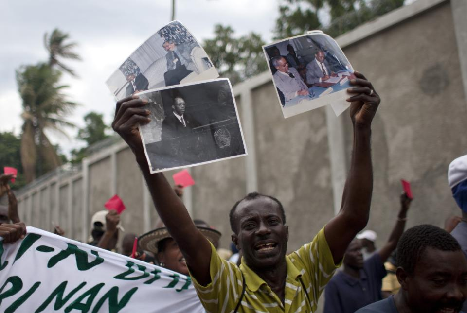 A demonstrator holds signs with images of former Haiti's President Jean Bertrand Aristide during a protest against Haiti's President Michel Martelly government in Port-au-Prince, Haiti, Sunday, Sept. 30, 2012. (AP Photo/Dieu Nalio Chery)