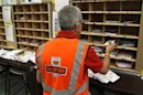 A Royal Mail worker sorts letters at the Edinburgh mail centre in Edinburgh, Scotland