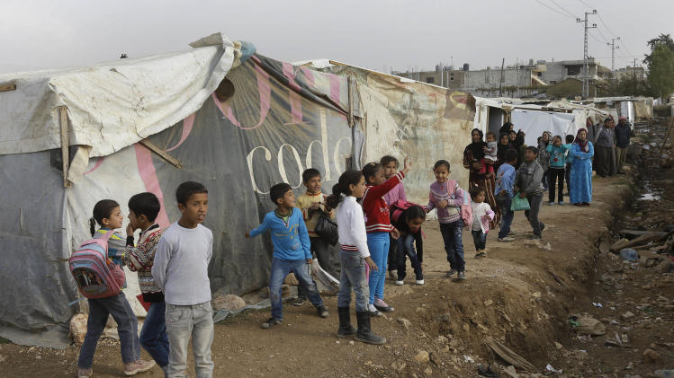 FILE - Syrian displaced children wait outside their tents for the arrival of French President Francois Hollande's companion Valerie Trierweiler, during her visit to one of the Syrian refugee camp, at Delhamiyeh village in the Bekaa valley, eastern Lebanon, in this Nov. 5, 2013 file photo. Thousands of refugees are fleeing border towns in central Syria where a high-stakes battle is raging, crossing valleys and ridges to reach safety in neighboring Lebanon, witnesses and the U.N. said on Sunday Nov. 17, 2013. (AP Photo/Hussein Malla, File)