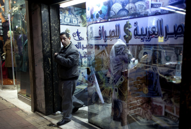 "A man leaves after changing foreign currency at a currency exchange office, in Cairo, Sunday, Jan. 6, 2013. The Arabic on the window reads: ""Arabian Egypt for Exchange.""  Egypt swore in 10 new ministe"