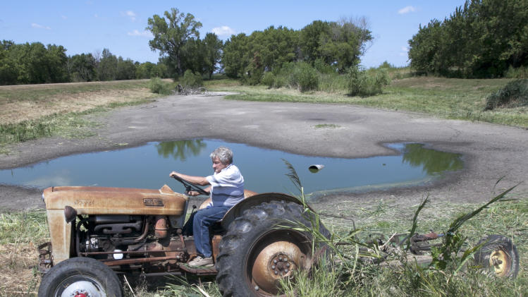 Jerry Johnson of Ashland uses his antique 57 Ford tractor to mow vegetation around his drying pond in Ashland, Neb., Thursday, Aug. 9, 2012, which he hopes will keep the critters away. The latest U.S. drought map shows that excessively dry conditions continue to worsen in the Midwest states that are key producers of corn and soybeans. This is the worst U.S. drought in decades. The weekly U.S. Drought Monitor map released Thursday, Aug. 9. 2012 shows that the area gripped by extreme or exceptional drought rose nearly 2 percent to 24.14 percent. (AP Photo/Nati Harnik)