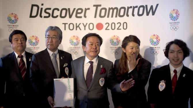 Naoki Inose, Governor of Tokyo, center, gestures to the media, with Teru Fukui, Minister in charge of sports, left, Tsunekazu Takeda, Tokyo 2020 President, Japanese Olympic Committee President and IOC Member, second left, Homare Sawa, Tokyo 2020 bid ambassador and soccer Olympian and Takayuki Suzuki, right, Tokyo 2020 bid ambassador and double bronze medalist in the London 2012 Paralympic Games, as they pose for the photographers following their first international presentation of their bid for the 2020 Olympic Games, in London, Thursday, Jan. 10, 2013. (AP Photo/Alastair Grant)