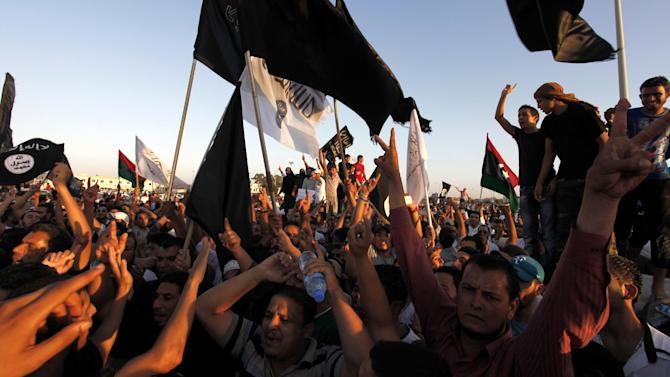 Libyan followers of Ansar al-Shariah Brigades and other Islamic militias hold a demonstration in Victory Square, against a film and a cartoon denigrating the Prophet Muhammad in Benghazi, Libya, Friday, Sept. 21, 2012. The attack that killed the U.S. ambassador and three other Americans has sparked a backlash among frustrated Libyans against the heavily armed gunmen, including Islamic extremists, who run rampant in their cities. more than 10,000 people poured into a main boulevard of Benghazi, demanding that militias disband as the public tries to do what Libya's weak central government has been unable to.(AP Photo/Mohammad Hannon)