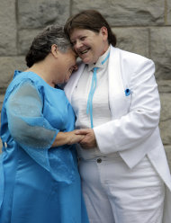 Dressed in their wedding attire, Kitty Lambert, left, and Cheryle Rudd, right, hug as they pose for a photo for a newspaper photographer before their wedding in Niagara Falls, N.Y., Saturday, July 23, 2011. The Buffalo couple wants Mayor Paul Dyster to pronounce them married one second after midnight _ the moment the law takes effect and makes New York the sixth and largest state to sanction gay marriage. (AP Photo/David Duprey)