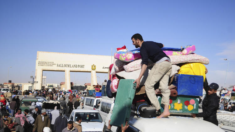 Egyptians, who have just crossed Salloum land port gate with Libya, at background, arrange their luggage on a mini bus, Wednesday, Feb.23, 2011. Turkey evacuated 3,000 citizens on two ships Wednesday from the chaos of Libya's uprising but thousands of other foreigners were still stranded at Tripoli airport, struggling to get a flight home.Several countries _ Russia, Germany and Ukraine among them _ sent more planes to help their citizens escape the turmoil engulfing the North African nation and the United States said Americans would be evacuated by ferry later Wednesday to the Mediterranean island of Malta.(AP Photo/Tarek Fawzy)