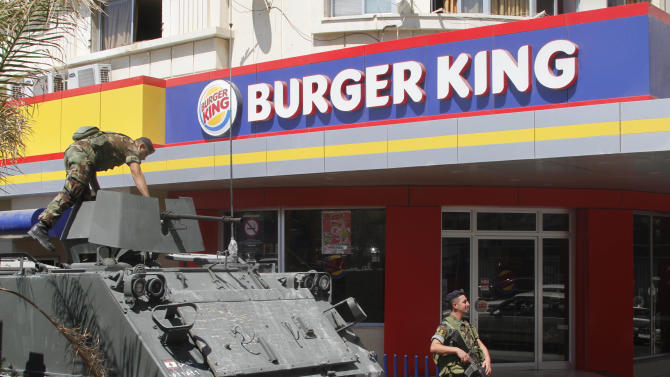 Lebanese army soldiers with their armored personnel carrier, stand guard outside a Burger King as part of stepped up security measures in the southern port city of Sidon, Lebanon, Saturday Sept. 15, 2012. Angry protesters attacked on Friday a Hardees and Kentucky Fried Chicken outlets in Tripoli north Lebanon to protest against a movie that insults Prophet Muhammad. (AP Photo/Mohammed Zaatari)