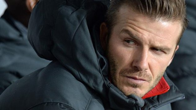 Paris Saint-Germain midfielder David Beckham sits on the bench during the Champions League match against Valencia (AFP)