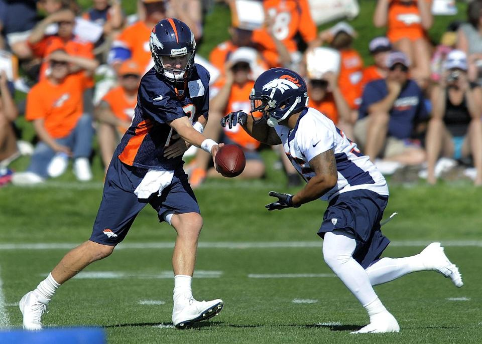Denver Broncos quarterback Peyton Manning (18) hands off to running back Lance Ball (35) during the opening session of Denver Broncos NFL football training camp in Englewood, Colo., Thursday, July 26, 2012. (AP Photo/Jack Dempsey)