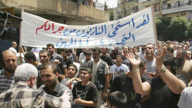 """Lebanese anti-Syrian regime protesters shout slogans during a demonstration to support the Syrian demonstrators who protest in Syria against Bashar Assad's regime, in Tripoli, northern Lebanon, on Friday July 1, 2011. Hundreds of thousands of protesters flooded cities around Syria on Friday in one of the largest outpourings against the regime of President Bashar Assad since the uprisings began more than three months ago. At least six people were killed in various clashes, activists said. The Arabic banner read:""""The Nazis are ashamed of your horrifying crimes"""". (AP Photo)"""