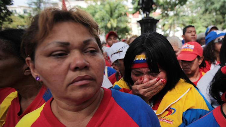 "A woman, right, reacts during a demonstration in support of Venezuela's President Hugo Chavez at the Simon Bolivar square in Caracas, Venezuela, Sunday Dec. 9, 2012. Chavez was heading back to Cuba on Sunday for more cancer surgery after announcing that the illness returned despite two previous operations, chemotherapy and radiation treatment.  Chavez said Saturday that if there are ""circumstances that prevent me from exercising the presidency further""  Vice-President Nicolas Maduro should replace him for the remainder of his term.(AP Photo/Fernando Llano)"