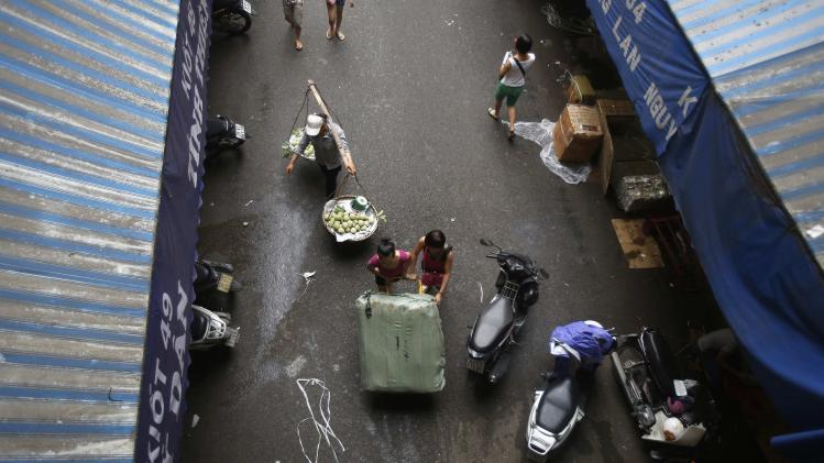 A fruit vendor walks behind women pushing a cart transporting fabric at Dong Xuan wholesale market in Hanoi