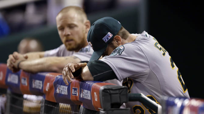 Oakland Athletics' Eric Sogard, left, and Brandon Moss sit in the dugout after the Athletics lost 9-8 to the Kansas City Royals in 12 innings in the AL wild-card playoff baseball game Tuesday, Sept. 30, 2014, in Kansas City, Mo. (AP Photo/Jeff Roberson)