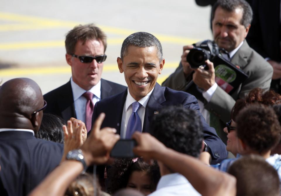 President Barack Obama greets people on the tarmac after arriving at John F. Kennedy International Airport, Monday, July 30, 2012, in New York. (AP Photo/Jason DeCrow)