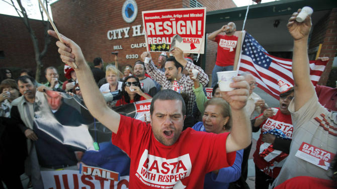 """FILE - This Sept. 21, 2010 file photo shows Jesus Casas, a member of the Bell Association to Stop The Abuse, or BASTA, which also means """"enough"""" in Spanish, joining other residents of the city of Bell, Calif., celebrating the arrest of current and former city officials on corruption charges, outside City Hall. an official of the city of Bell, Calif. Jury selection begins Tuesday, Jan. 15, in the trial of former officials of the scandal ridden city of Bell in a massive corruption case that nearly bankrupted the working-class Los Angeles suburb.  (AP Photo/Reed Saxon, File)"""