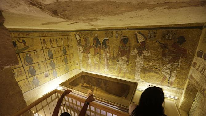 FILE -- In this Thursday, Nov. 5, 2015 file photo, tourists look at the tomb of King Tut as it is displayed in a glass case at the Valley of the Kings in Luxor, Egypt. On Saturday, Nov. 28, 2015, Egyptian Antiquities Minister Mamdouh el-Damaty said there is a 90 percent chance that hidden chambers will be found within King Tutankhamun's tomb, based on the preliminary results of a new exploration of the 3,300-year-old mausoleum. (AP Photo/Amr Nabil, File)