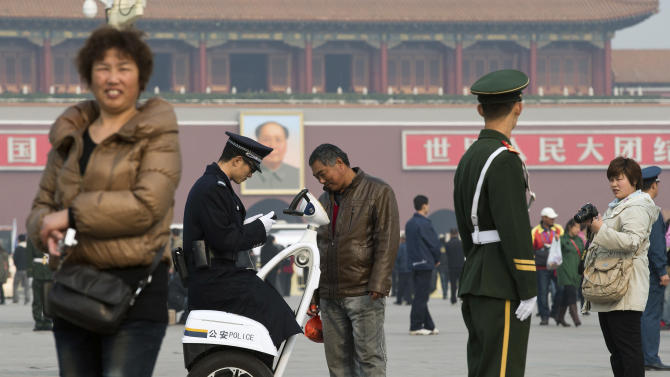 In this photo taken Nov. 2, 2012, a Chinese police officer checks the identity card of a visitor on Tiananmen Square in Beijing. Authorities want no more surprises as party leaders convene in the capital, and rights groups say the wide-ranging crackdown on critics bodes poorly for those who hope the incoming generation of leaders will loosen restrictions on activism. (AP Photo/Andy Wong)