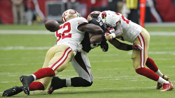 Arizona Cardinals running back Andre Ellington (38) is unable to hold onto the ball as San Francisco 49ers inside linebacker Patrick Willis (52) and Jimmie Ward (25) defend during the first half of an NFL football game, Sunday, Sept. 21, 2014, in Glendale, Ariz. (AP Photo/Ross D. Franklin)