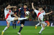 Barcelona forward Lionel Messi (C) is blocked by Rayo Vallecano's Jordi Figueras Montel (L) and Tito during their Spanish league match on March 17, 2013. Messi and teammate David Villa combined for all of Barca's goals in the 3-1 win over Rayo