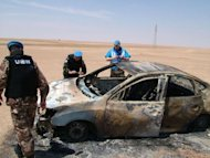"A handout picture released by the official Syrian Arab News Agency (SANA) on May 14, shows UN observers inspecting a burnt car which was targeted in Deir Ezzor. A convoy of UN truce observers came under attack in a Syrian town on Tuesday during a funeral procession in which a monitoring group said regime forces ""massacred"" 20 people"
