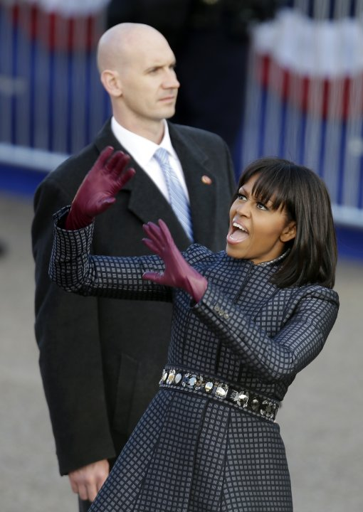 First lady Michelle Obama reacts to the crowd as she walks the inaugural parade route walk down Pennsylvania Avenue en route to the White House, Monday, Jan. 21, 2013, in Washington. Thousands  marche