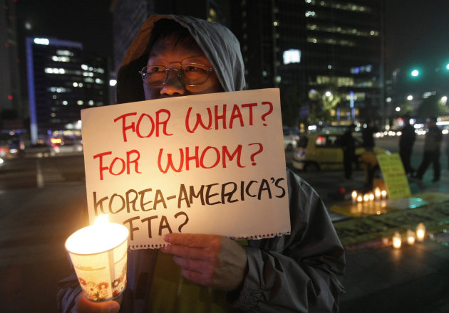 A South Korean protester participates in a rally against a free trade agreement (FTA) between South Korea and the United States near the U.S. Embassy in Seoul, South Korea, Wednesday, Oct. 12, 2011. South Korean President Lee Myung-bak left for the United States on Tuesday for talks with U.S. President Barack Obama as Congress is set to endorse a long-pending free trade agreement with Seoul, a landmark deal expected to bring the two allies further closer together. (AP Photo/Ahn Young-joon)