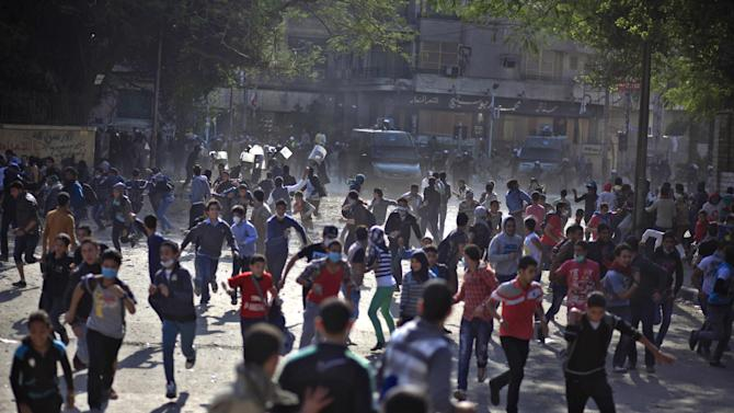 Egyptian protesters clash with security forces near Tahrir square, in Cairo, Egypt, Wednesday, Nov. 28, 2012. Egyptian state television says the country's highest appeal court has decided to suspend its work nationwide to protest the president's decrees giving himself nearly absolute powers. (AP Photo/Khalil Hamra)