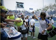 David Ferrer of Spain gives a thumbs up as fans clamor for his autograph after he defeated Mikhail Kukushkin of Kazakhstan at the U.S. Open tennis championships in New York August 31, 2013. REUTERS/Eduardo Munoz
