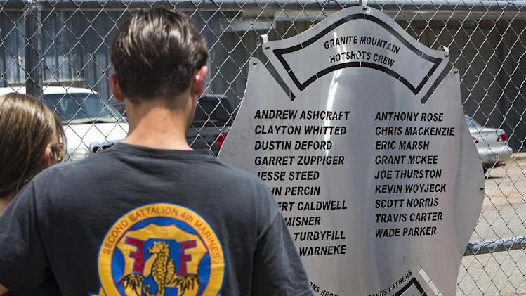 A plaque is posted on a fence outside Fire Station 7 in Prescott, Ariz. on Tuesday, July 2, 2013 in a makeshift memorial for the 19 Granite Mountain Hotshots who were killed by an out-of-control blaze near Yarnell, Ariz. on Sunday. (AP Photo/The Arizona Republic, Tom Tingle)