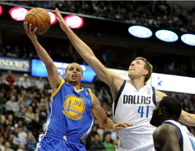 Golden State Warriors point guard Stephen Curry (30) drives to the basket on Dallas Mavericks power forward Dirk Nowitzki (41) in the second half during an NBA basketball game on Wednesday, Nov. 27, 2