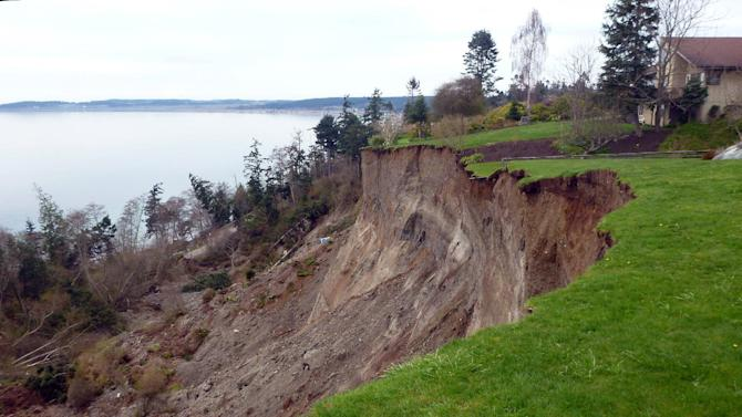 This March 27, 2013 photo provided by the Washington Dept. of Natural Resources, shows a home near the edge of a massive landslide that damaged one home and isolated or threatened more than 30 others near Coupeville, Wash.  Geologists and engineers are assessing what might happen next after a large landside thundered down the scenic island hillside overlooking Puget Sound. (AP Photo/Washington Dept. of Natural Resources, Stephen Slaughter)