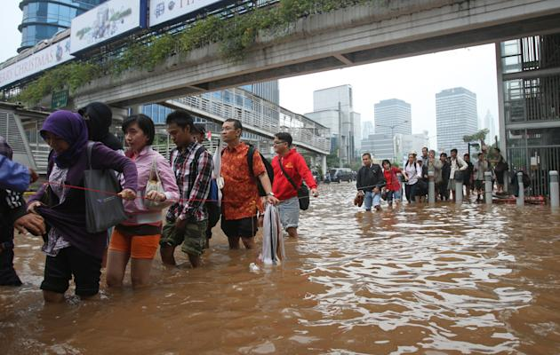 People cross a flooded street while holding a cord for safety in Jakarta, Indonesia Friday, Jan. 18, 2013. Indonesia's army deployed rubber boats in the capital's business district on Thursday to resc