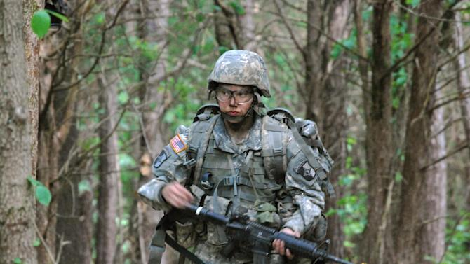 In this May 9, 2012 photo, Capt. Sara Rodriguez of the 101st Airborne Division walks through the woods during the expert field medical badge testing at Fort Campbell, Ky.   (AP Photo/Kristin M. Hall)