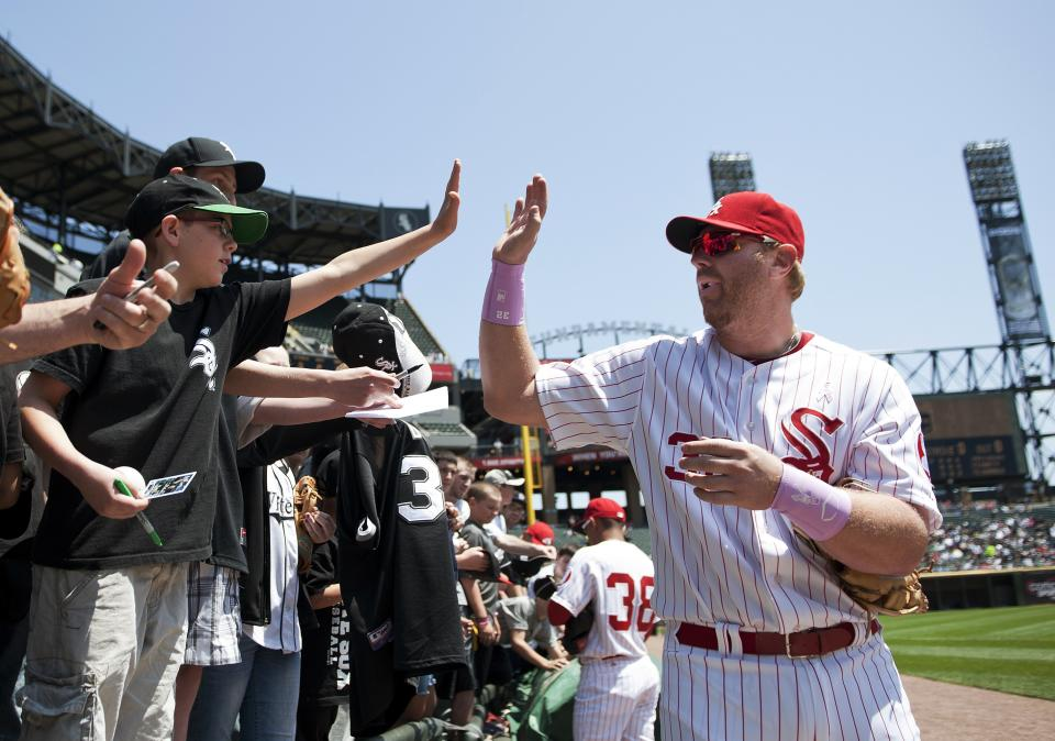 Chicago White Sox designated hitter Adam Dunn, right, high-fives Andrew Nieman, 10, after signing autographs for fans before the White Sox's baseball game against the Kansas City Royals, Sunday, May 13, 2012 in Chicago. The Royals won 9-1. (AP Photo/Brian Kersey)