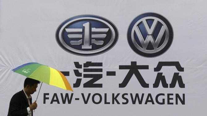 File photo of a man holding an umbrella as he walks past a company logo of FAW-Volkswagen at an automobile exhibition in Fuyang