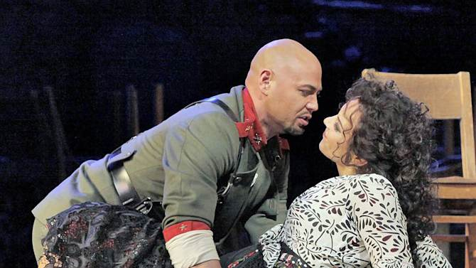 """In this undated photo provided by the Metropolitan Opera, Keith Miller, left, plays Zuniga in Bizet's """"Carmen"""" with Elina Garanca in the title role at the Metropolitan Opera in New York. Miller, a former University of Colorado fullback, has reinvented himself, going from the gridiron to the stage and will appear in Verdi's """"Un Ballo in Maschera,"""" at the Metropolitan Opera. Performances begin Thursday, Nov. 8, 2012. (AP Photo/Metropolitan Opera, Ken Howard)"""