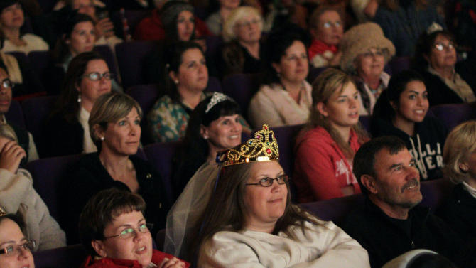 """FILE - In this April 29, 2011, file photo, Sandy Weimer, wearing tiara, and Cathy Dettman, left, attend a royal wedding """"hat and pajamas"""" party at the Cameo Cinema in St. Helena, Calif., where more than150 people filled the theater in the middle of the night to watch a live broadcast of the royal wedding of Britain's Prince William and Kate Middleton. The palace announced Monday, Dec. 3, 2012, that Prince William and wife Kate are expecting their first child_and it seems at times that Americans may be more enthralled than the Brits. There are several reasons for the American public's pleasure in Kate's news, manifested not only by the good wishes sent by President Obama but also by the breathless news coverage and the general good will toward the couple. (AP Photo/Eric Risberg, File)"""