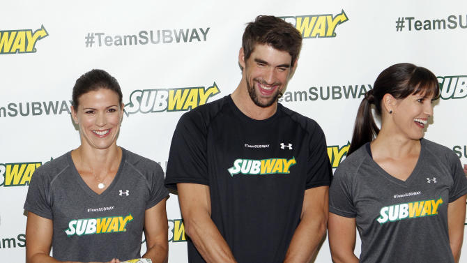 Whitney Phelps, left, is joined by her bother, Olympic swimming champion Michael Phelps, and sister Hilary as as she announces that she will run the ING New York City Marathon with Team SUBWAY at the Chelsea Piers Sport Center, Monday, Oct. 15, 2012 in New York. (Photo by Jason DeCrow/Invision for SUBWAY/AP Images)