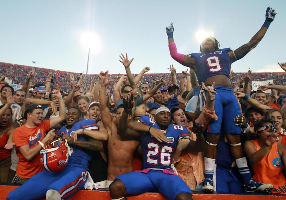 Florida defensive backs Marcus Roberson, left, De'Ante Saunders (26) and Josh Evans (9) celebrate with fans after defeating LSU 14-6 in an NCAA college football game Saturday, Oct. 6, 2012, in Gainesville, Fla. Florida won 14-6.(AP Photo/John Raoux)