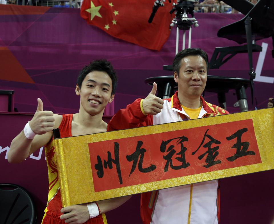 "Chinese gymnast Zou Kai and his coach hold a banner which reads ""Five Gold Crown Nine Provinces"" after Zou Kia won the gold for the men's floor exercise finals at the 2012 Summer Olympics, Sunday, Aug. 5, 2012, in London. (AP Photo/Julie Jacobson)"