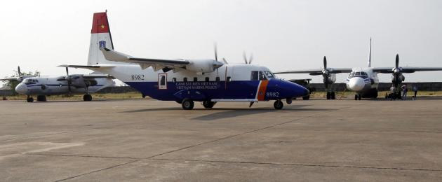 Vietnam Marine Police Casa 212 aircraft taxies past a Vietnam Air Force search and rescue aircraft An-26 at a military airport in Vietnam's Ho Chi Minh City