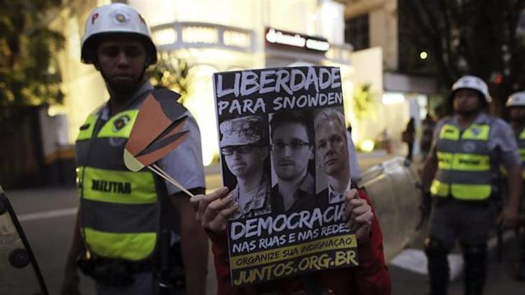 A student of the University of Sao Paulo (USP) holds a poster bearing pictures of U.S. Army Private First Class Bradley Manning, former U.S. spy agency contractor Edward Snowden and Wikileaks founder Julian Assange (L-R) in front of military police during a protest against Sao Paulo State Governor Geraldo Alckmin, in Sao Paulo October 9, 2013. REUTERS/Nacho Doce