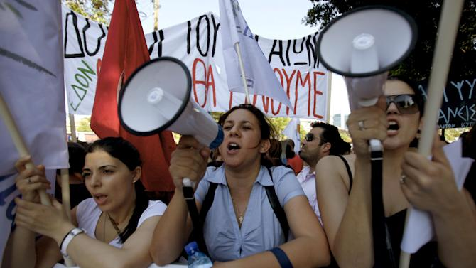 Protester shout slogans during an anti-bailout protest outside of the Cyprus' parliament in capital Nicosia, Tuesday, April 30, 2013. Cyprus' lawmakers are voting Tuesday on a multi-billion bailout agreement aimed at preventing the country from going bankrupt. The 56-seat parliament is expected to narrowly approve the 23 billion-euro ($30 billion) deal that the country struck with its euro partners and the International Monetary Fund last month. (AP Photo/Petros Karadjias)