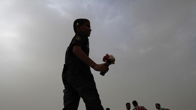 "A Bahraini anti-government protester carries flowers in a spent tear gas canister at a march in the northern village of Saar, Bahrain, on Friday, April 5, 2013. Demonstrators shouted ""down with the government"" during the march, called by several opposition groups demanding freedom for political prisoners and democracy in the Gulf island kingdom. (AP Photo/Hasan Jamali)"
