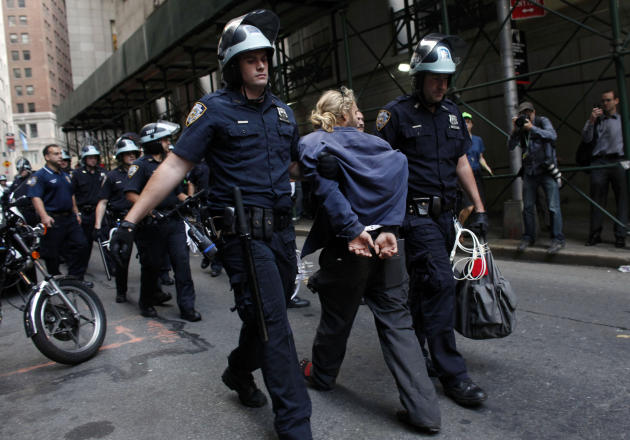 Police officers lead a man away during an Occupy Wall Street march, Monday, Sept. 17, 2012, in New York. A handful of Occupy Wall Street protestors were arrested during a march on the New York Stock E