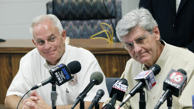Harrison County Emergency Management Agency Director Rupert Lacy, left, listens as Gov. Phil Bryant discusses Gulf Coast preparations for Tropical Storm Isaac during a news conference at the Harrison County Emergency Operations Center in Gulfport, Miss., Monday, Aug. 27, 2012. (AP Photo/Rogelio V. Solis)